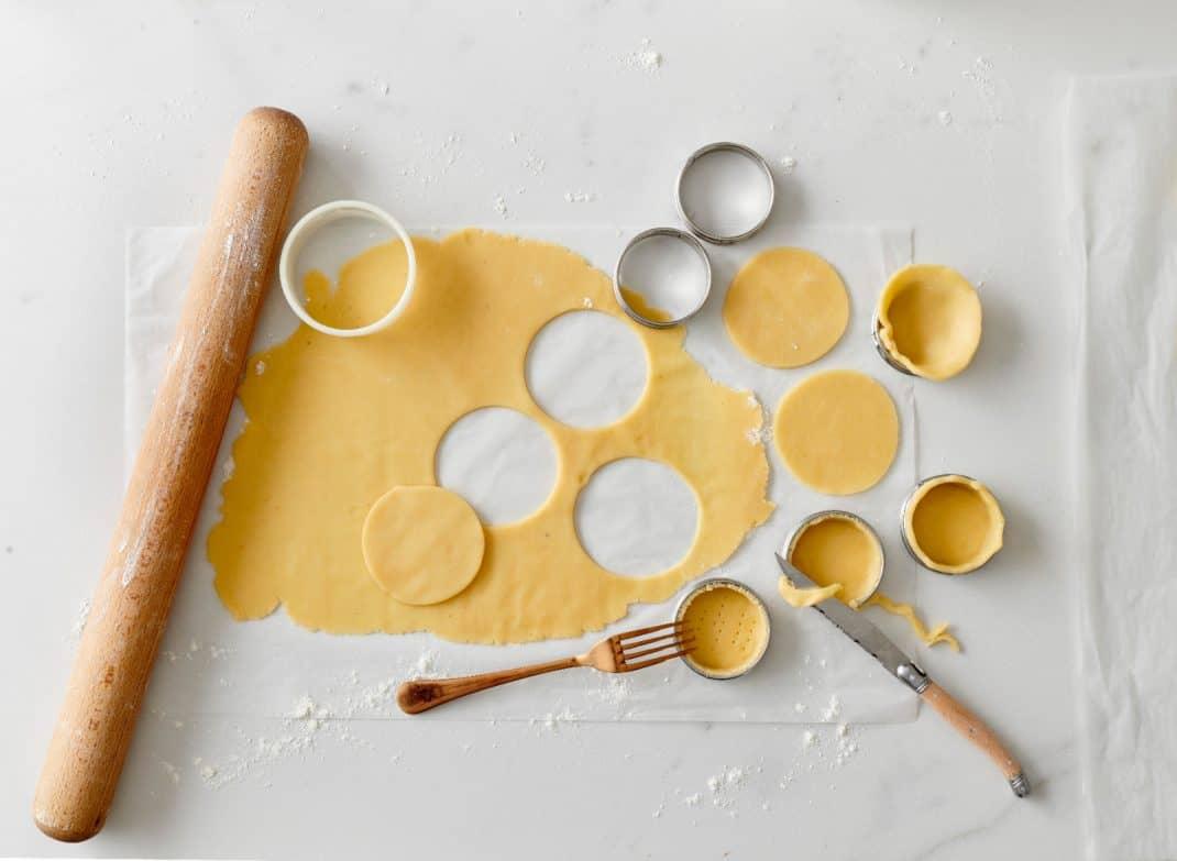 Deeg uitsteken in vormpjes doen uit het kookboekje Nog Meer Kleine Taartjes van Meike Schaling